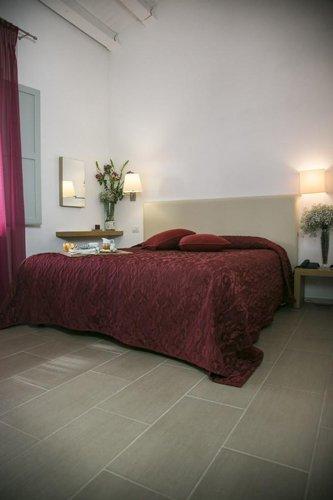 stanza con letto matrimoniale con copriletto bordeaux