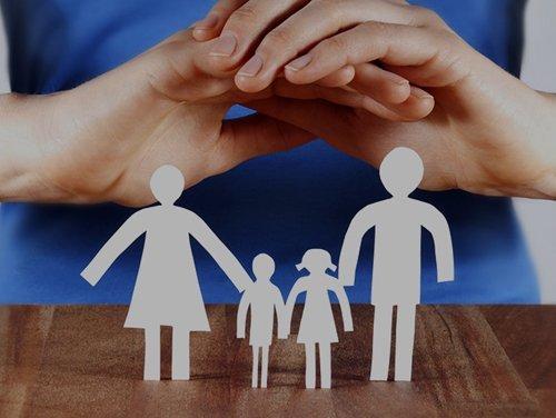 due mani coprono una famiglia fatta con della carta