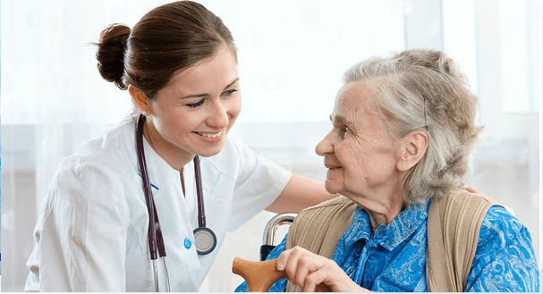 donna anziana sulla sedia a rotelle viene assistita da una dottoressa