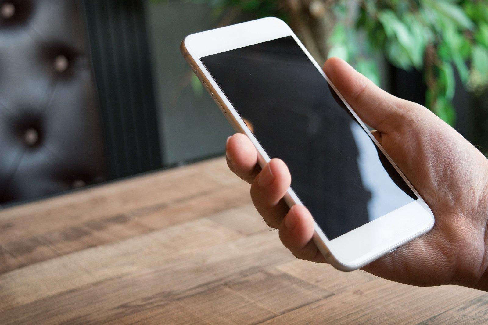 una mano con uno smartphone bianco
