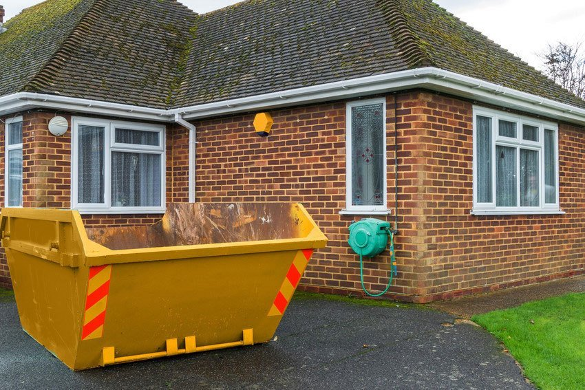 A skip in the driveway of a bungalow