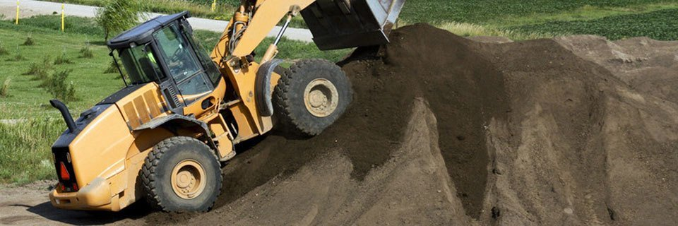 A yellow tipper truck on a large mound of topsoil