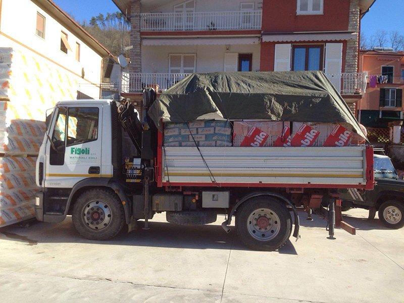 un camion con il rimorchio carico e sopra un telone nero