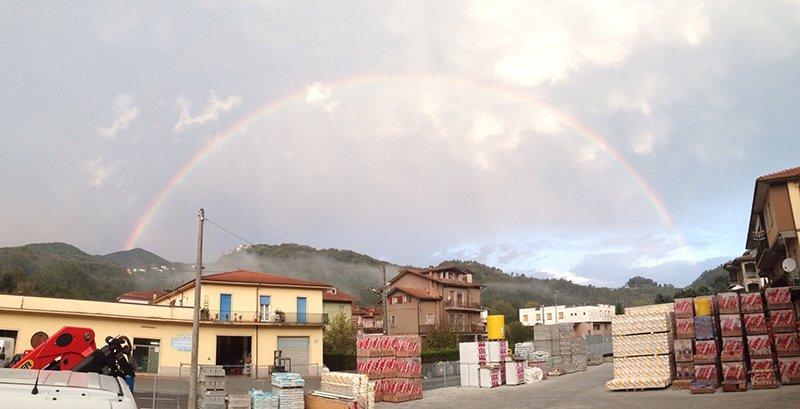 esterno di un magazzino con delle scatole, confezioni di materiale sui bancali e vista di alcune case e del paesaggio montuoso con l'arcobaleno