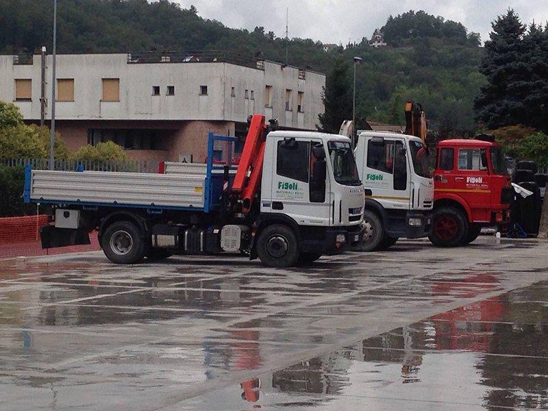tre camion parcheggiati, due di color bianco e uno rosso