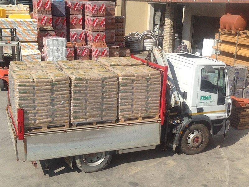 Un camion con il rimorchio carico di sacci di pellet e dietro vista di altro materiale su dei bancali