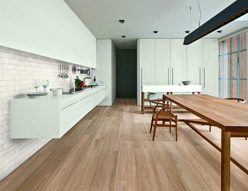 Una cucina sulla sinistra piano cottura e lavandino, sulla destra un tavolo lungo  di legno  e infondo un mobile bianco