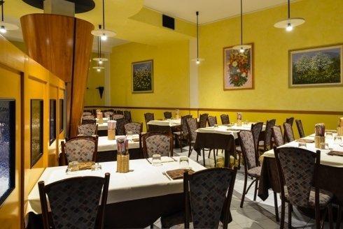 Tavole e sedie classiche e la parete gialla con acquarelli