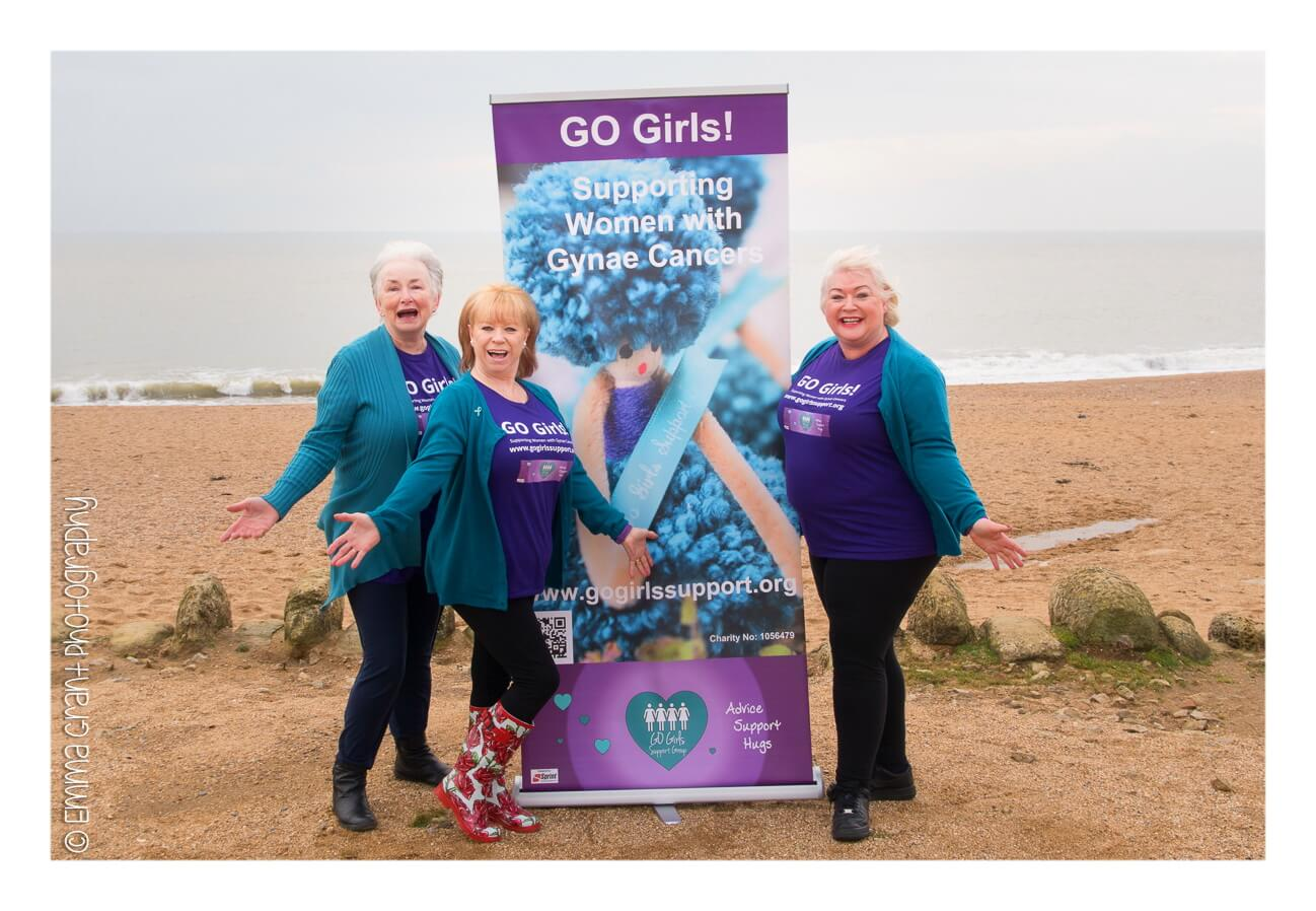 go girls members next to a banner at the beach