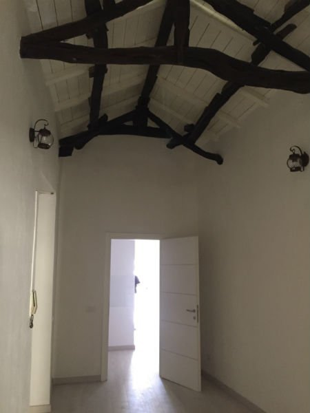 un soffitto con travi di tronchi di legno e una porta aperta