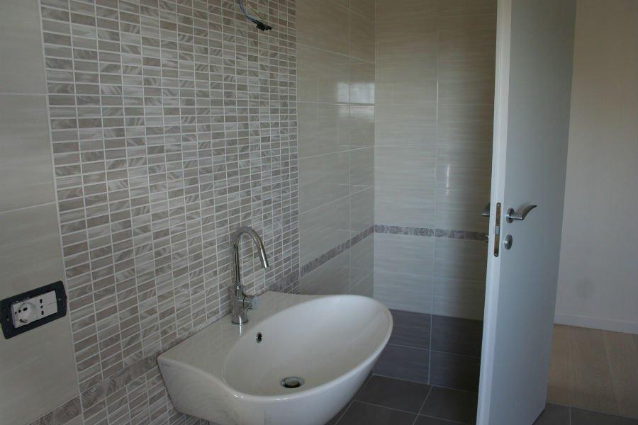 un lavabo e delle piastrelle bianche e beige a muro