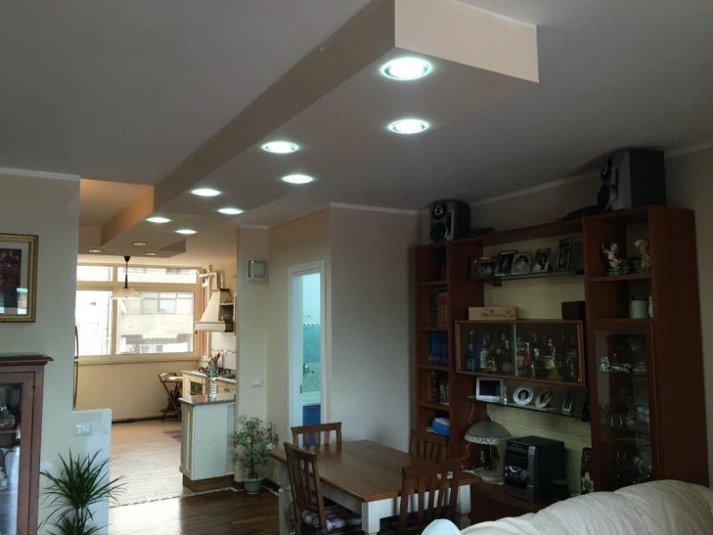 una sala con un tavolo, un mobile marrone con delle vetrine e faretti sul soffitto