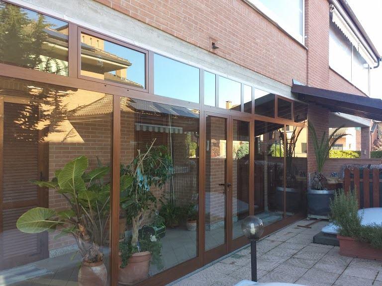 una vetrata con finiture in legno, una porta e vista di alcuni vasi con delle piante
