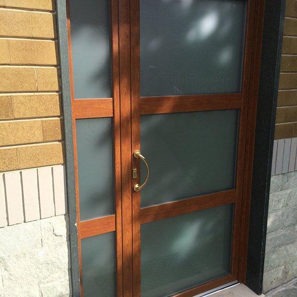 una porta di  vetro con finiture in legno