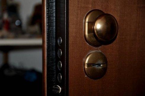 una porta in legno con un pomello dorato vista da vicino