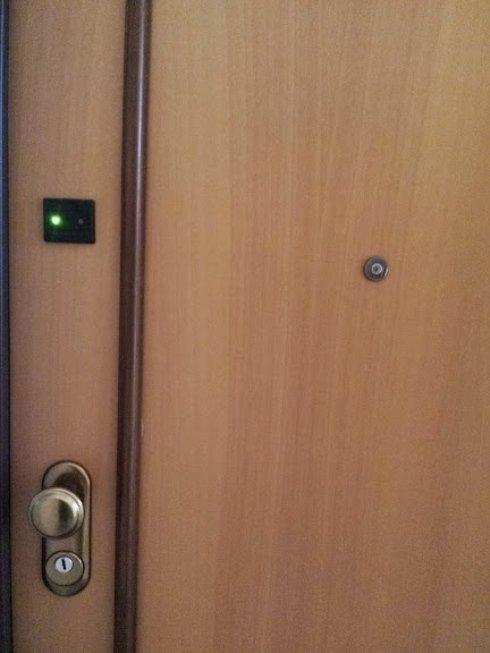 una porta in legno chiaro con vista di uno spioncino e una maniglia