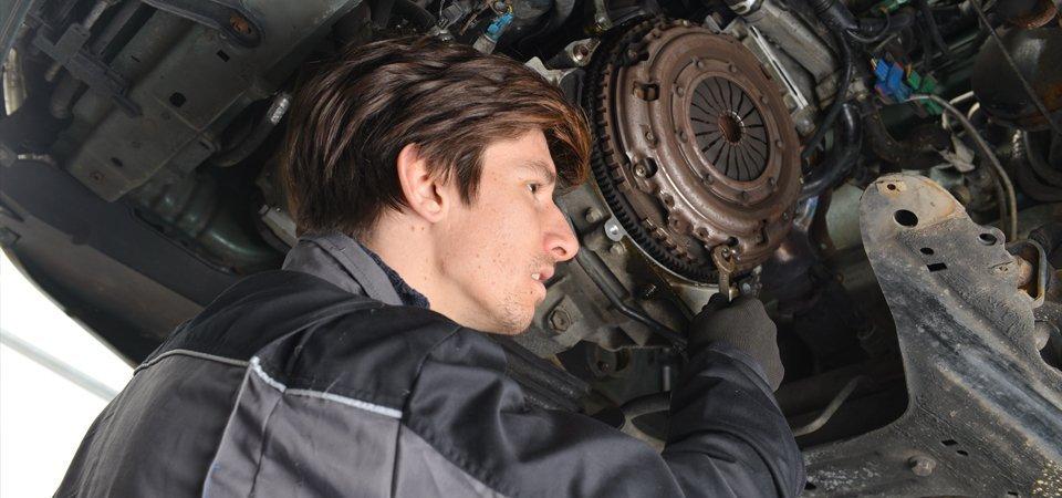 mechanic repairing a vehicle's clutch