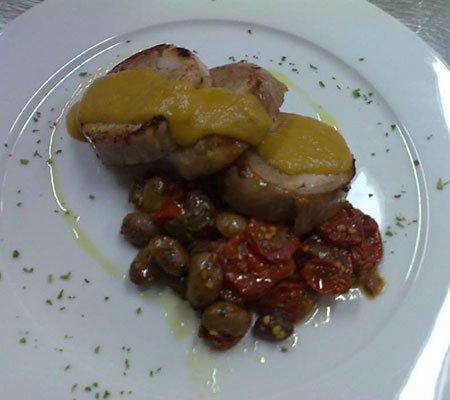 un piatto a base di fette di carne, pomodorini e olive