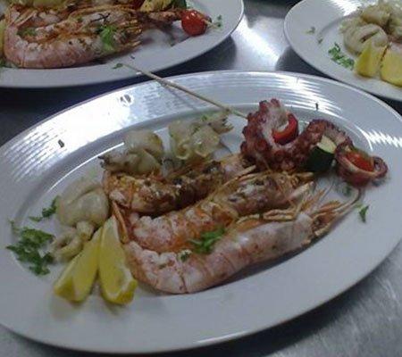 un piatto a base di scampi, involtini di polpo e calamar