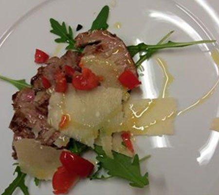 un piatto a base di carne con rucola, grana e pomodorini