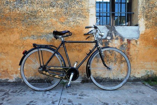 Bicicletta artigianale nera appoggiata al muro su misura
