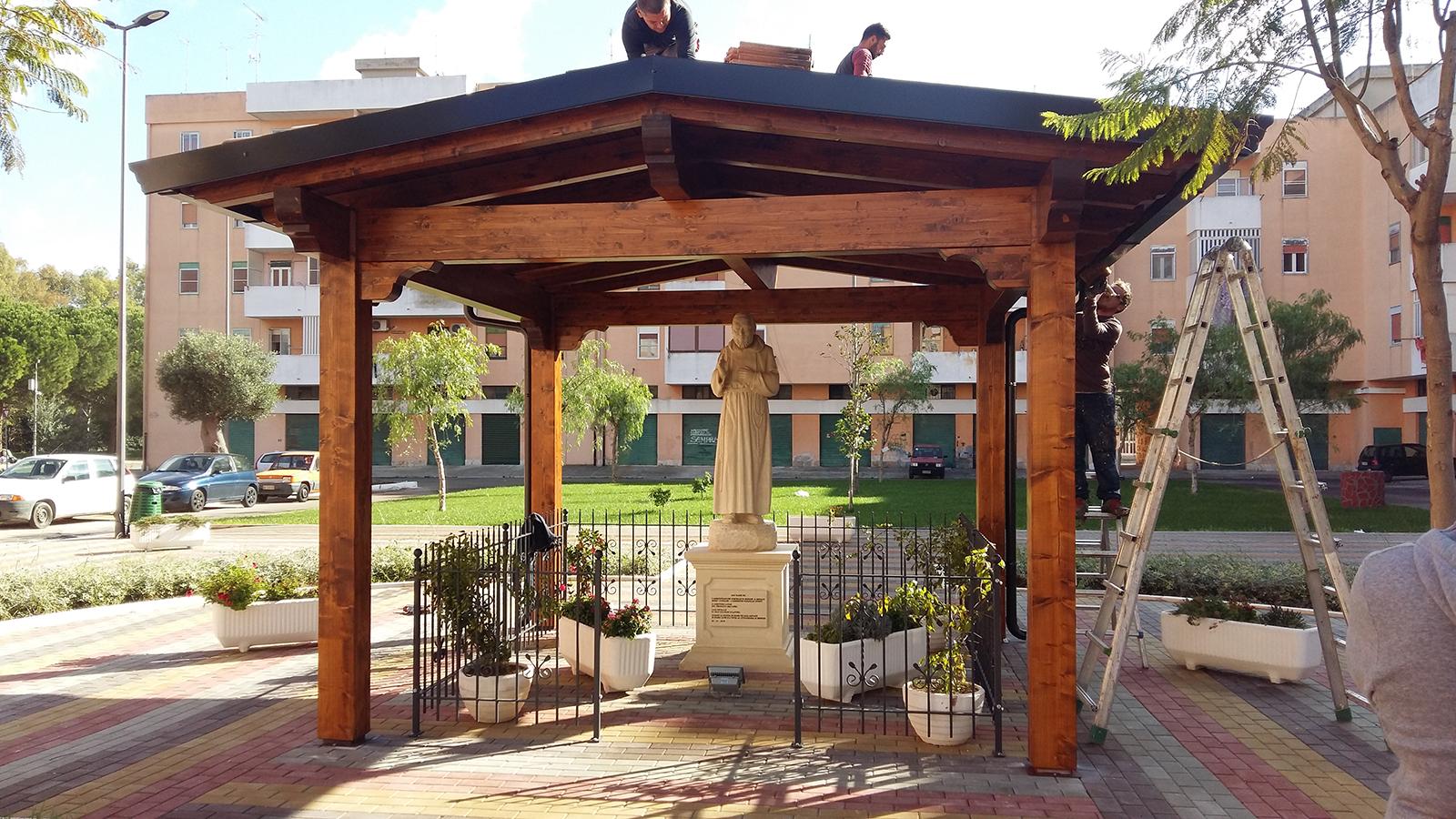 un gazebo in legno con sotto una statua di Gesu'