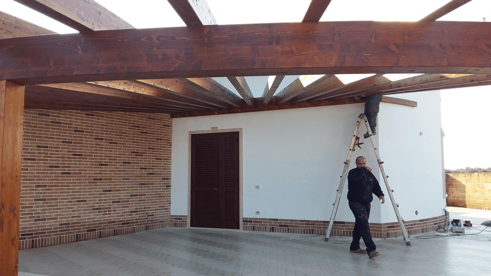 delle travi di una copertura in legno, un operaio e una scala