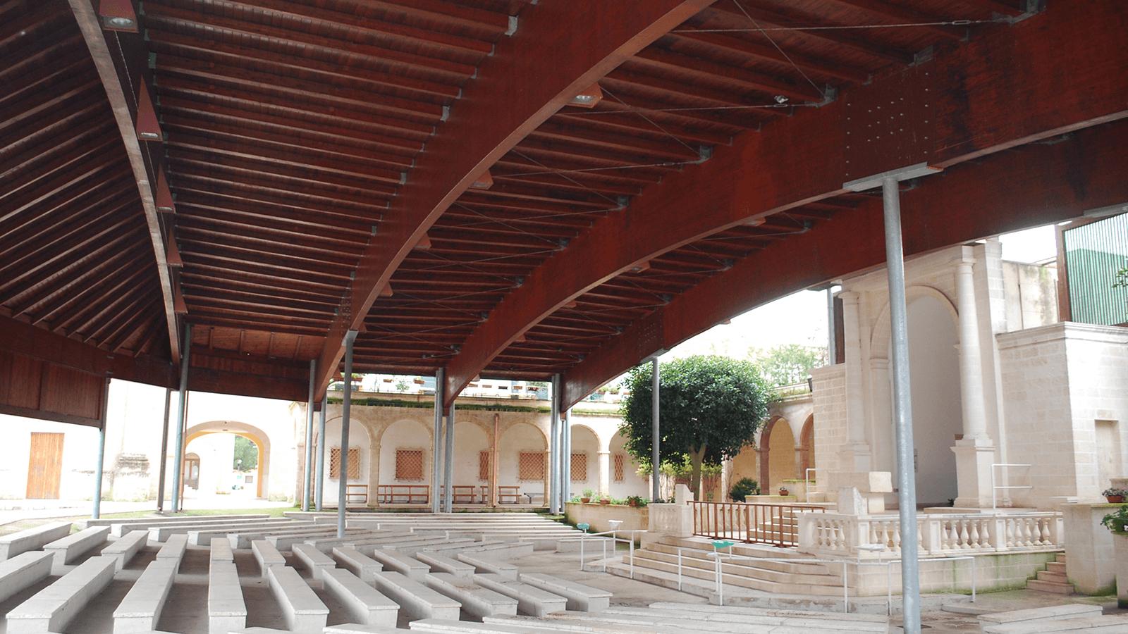 una grossa copertura in legno e sotto della panchine in marmo