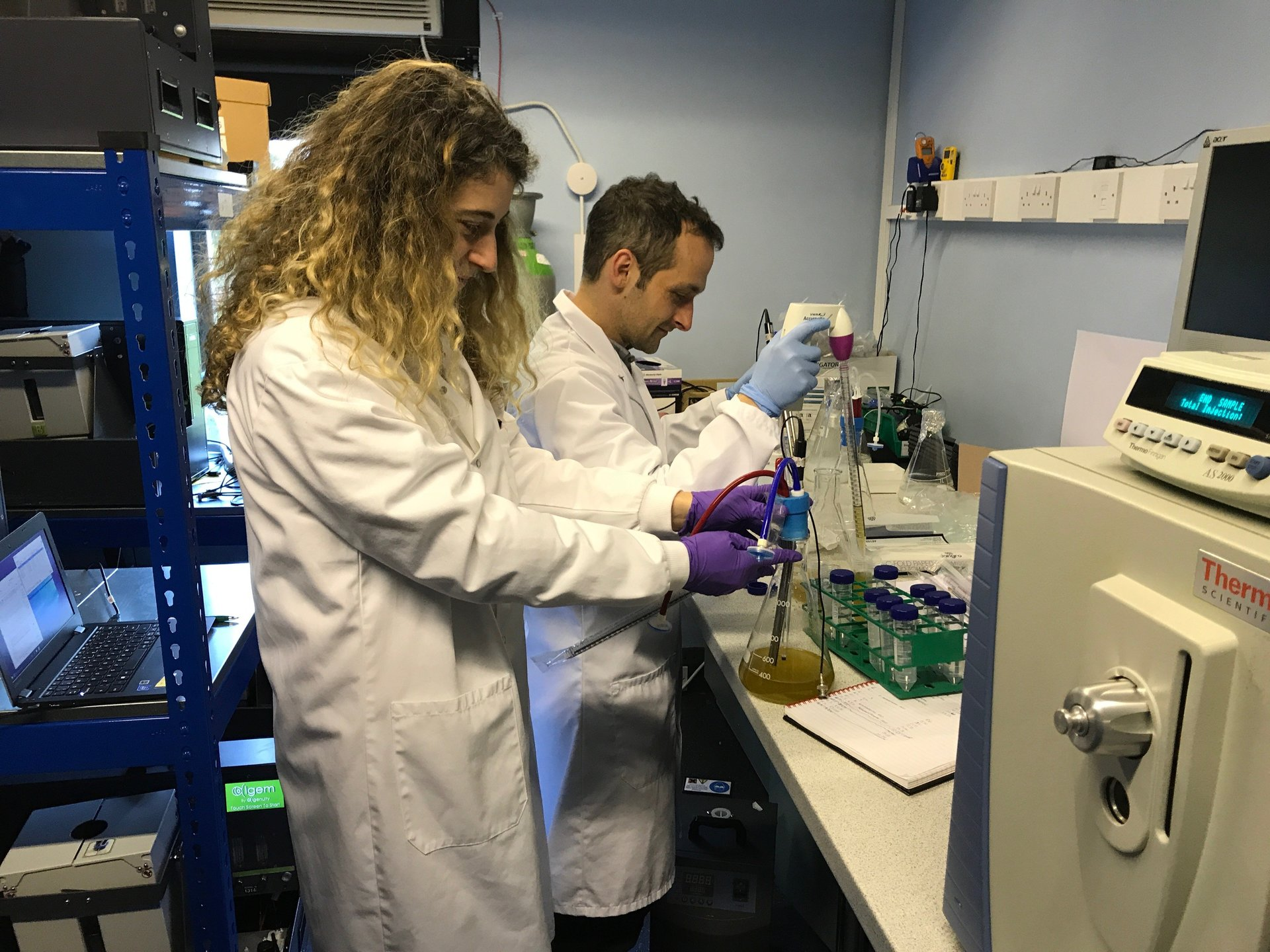Male and Female Scientist working with algae cultures in Erlenmeyer flasks