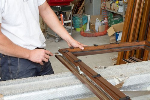 fabbro che utilizza un cacciavite per sistemare una finestra