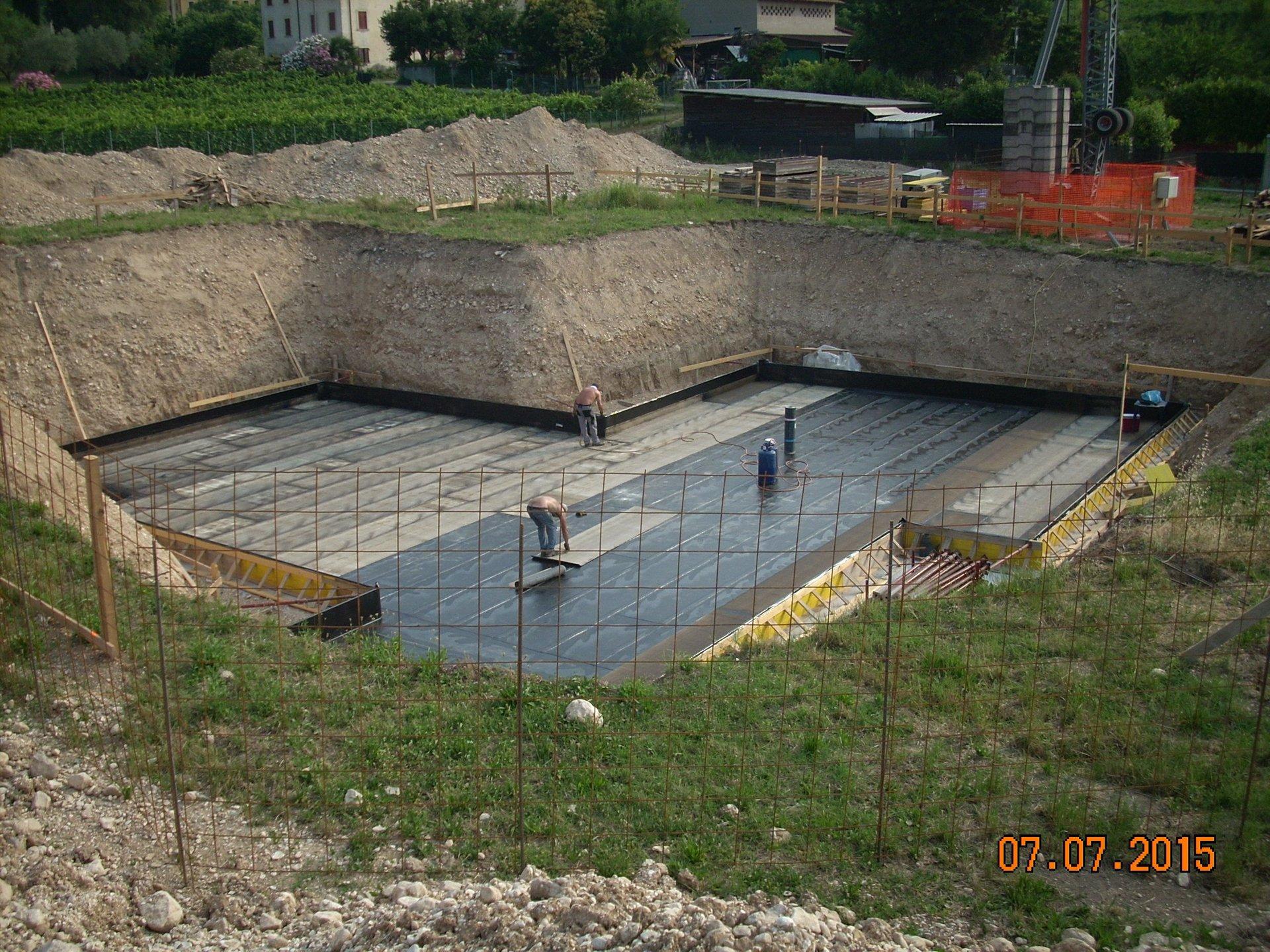 uomini al lavoro in un piccolo cantiere mentre stendono degli strati impermeabili