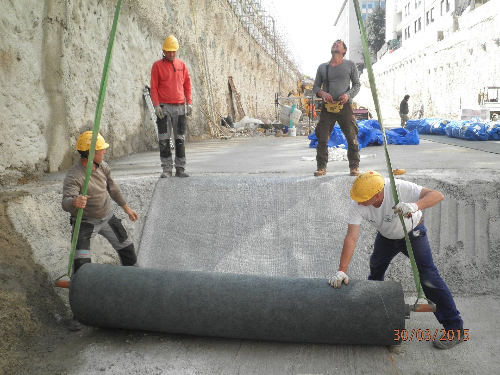 dei muratori che stendono un rotolo di tessuto impermeabili