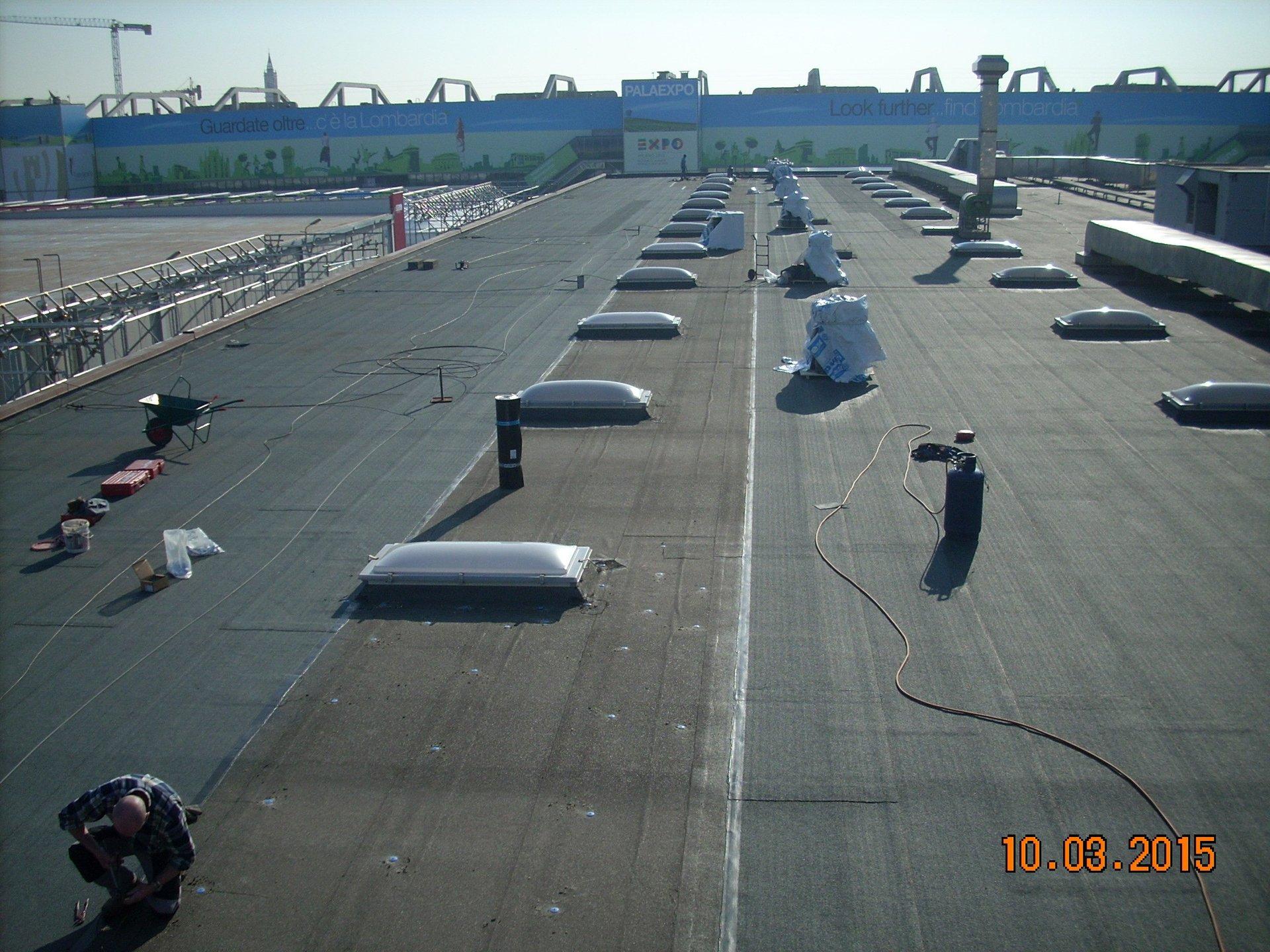 un uomo chinato a terra al lavoro e un tetto completamente impermeabilizzato