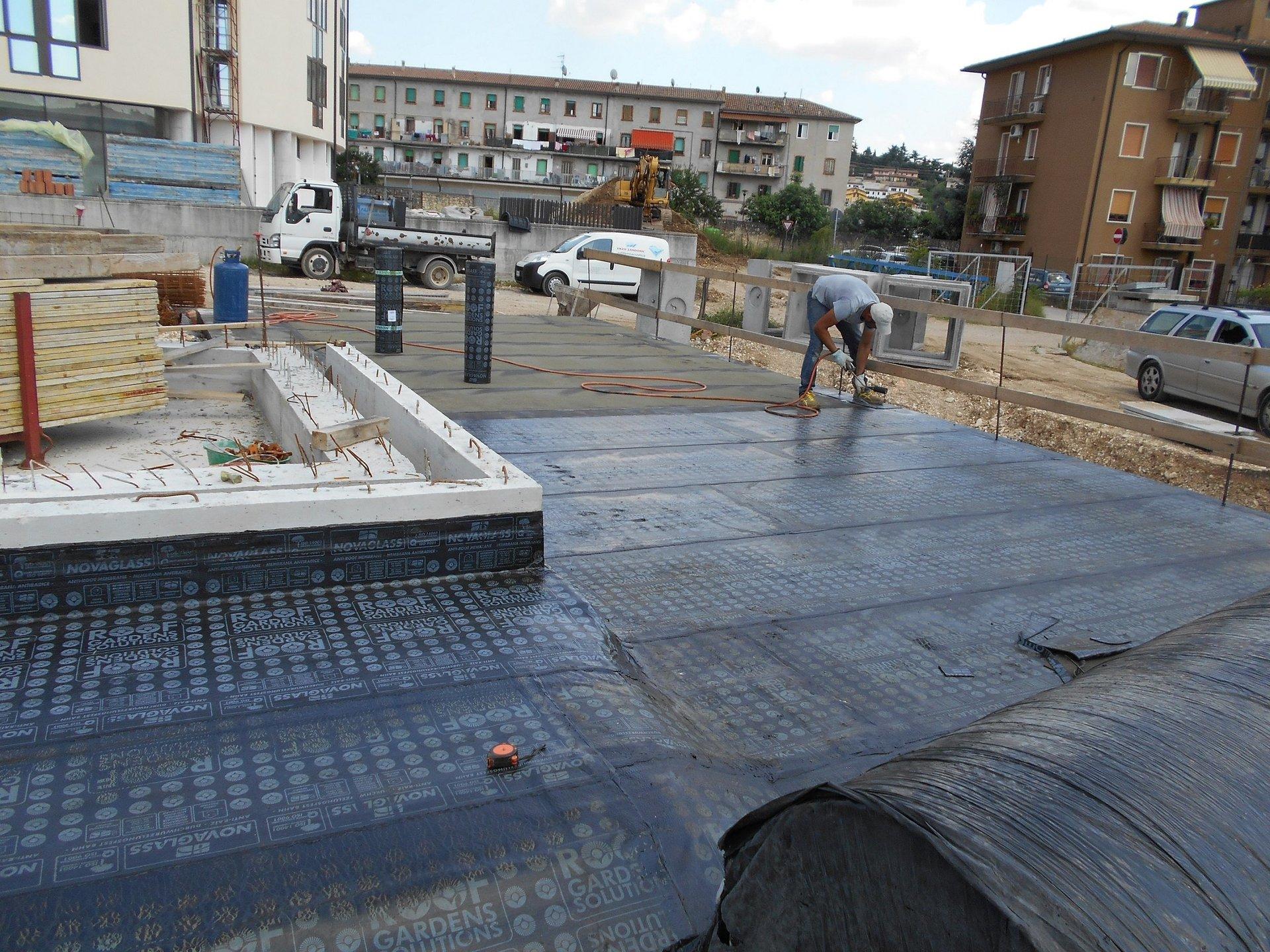un uomo chinato in avanti al lavoro in un'area di lavori in corso e del tessuto impermeabilizzato sulla struttura