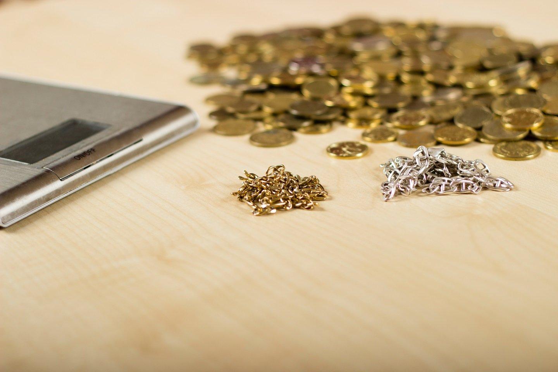Catenine e monete in oro e argento su una scrivania con bilancino