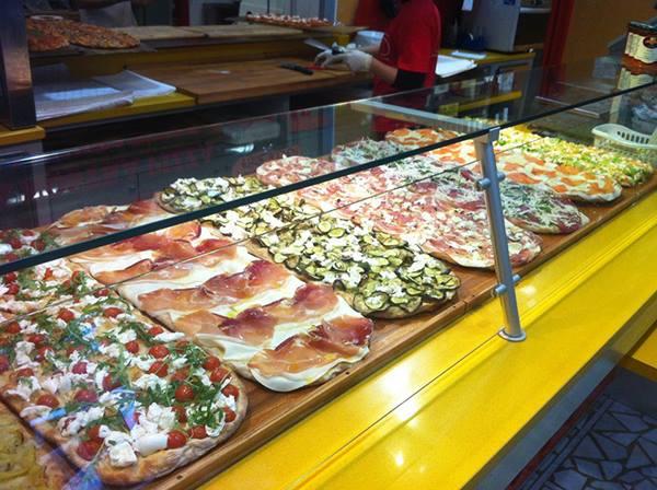 delle pizze al metro di diversi gusti esposte in una vetrina