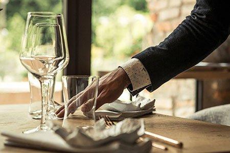 una mano di un uomo mentre apparecchia un tavolo