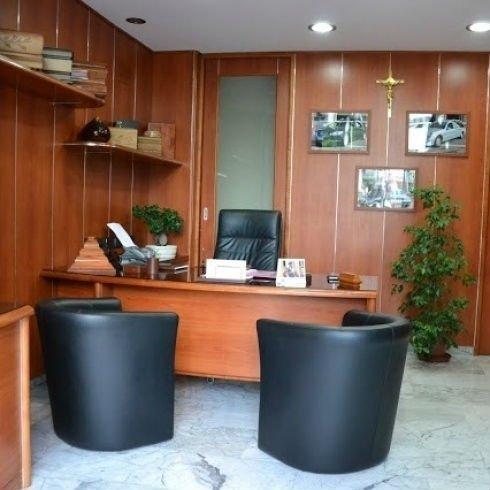 un ufficio con una scrivania e tre sedie nere