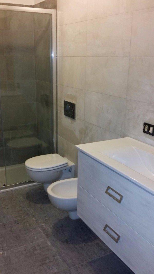 un bagno con box doccia, Wc bidet e un mobile bianco sotto un lavabo