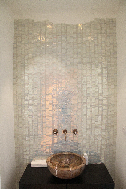 un lavabo in marmo di color marrone e un muro con delle piastrelline a effetto perla