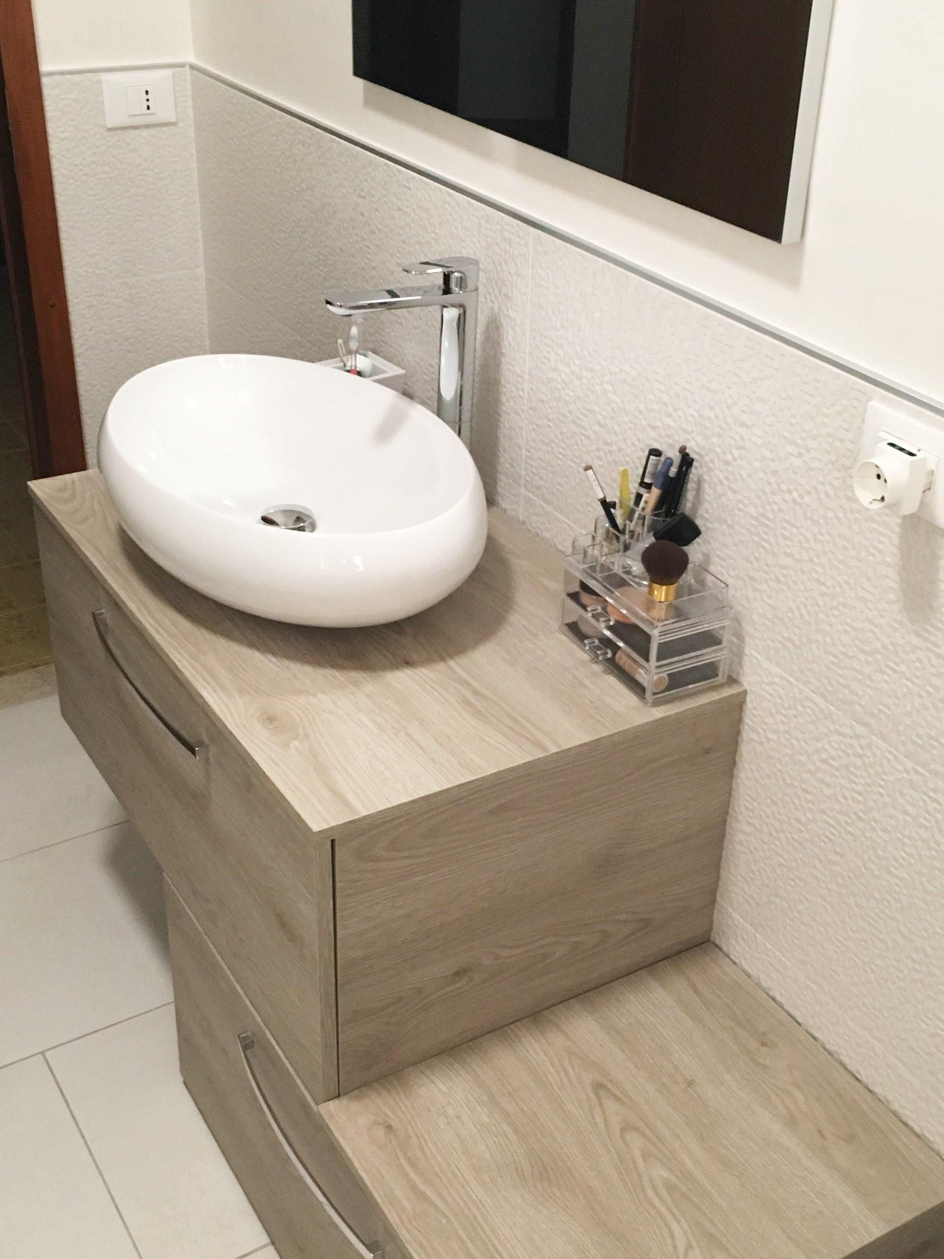 un lavabo ovale e due cassetti in legno chiaro