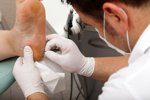 Podiatrist treating foot of a patient