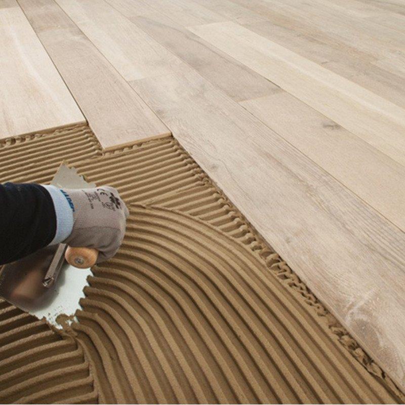 una mano che usa una spatola su del cemento e accanto un parquet