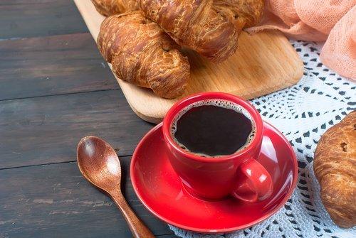 caffeè e cornetto su un tavolo di legno
