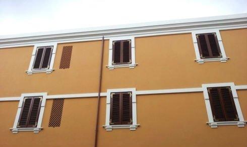 una casa con delle persiane in legno alle finestre