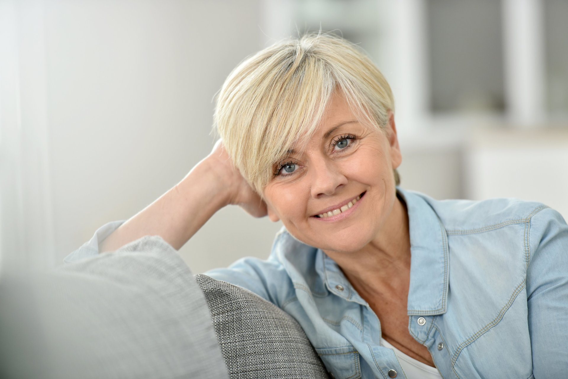 Smiling middle aged woman on couch