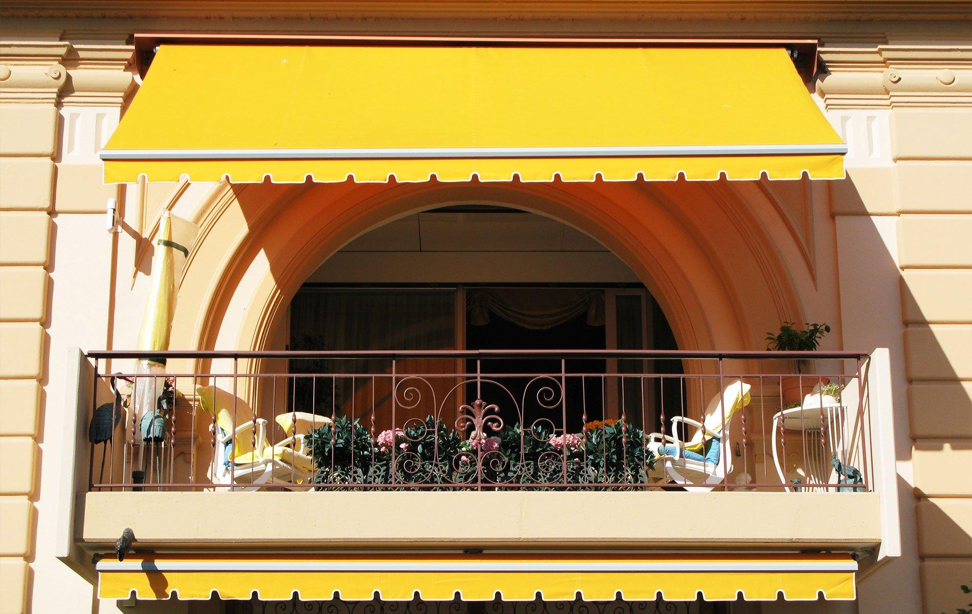 un balcone con due poltrone e una tenda da sole di color giallo