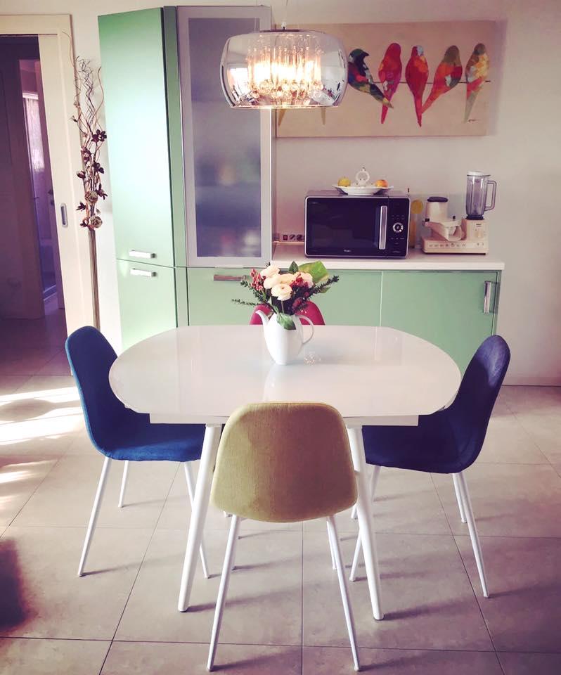 un mobile da cucina di color verde e un tavolo con sedie multicolori