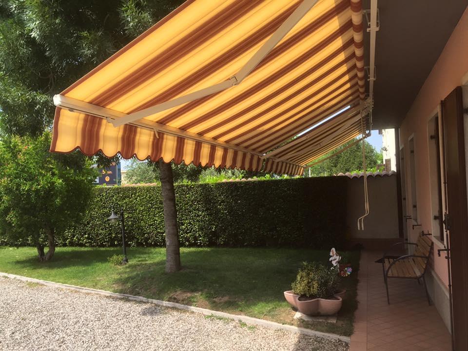 una villa con vista di una tenda da sole e una panchina sotto