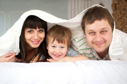 Famiglia boca sotto nel materasso e coperta con un lenzuolo